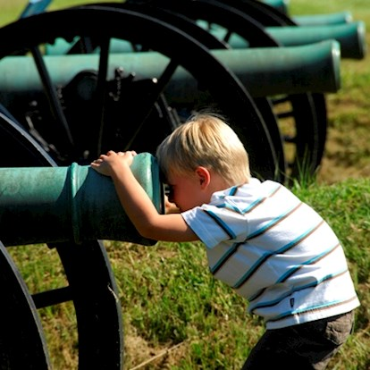 Child looking down cannon at a National Military Park in Vicksburg, MS
